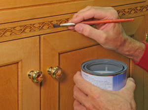 Closeup of painter apply vanish to inlaid trim